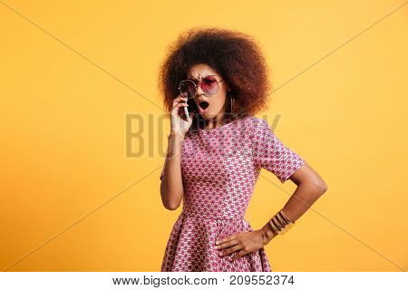 Portrait of an angry furious afro american woman in retro style clothes talking on mobile phone while standing isolated over yellow background