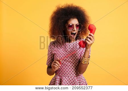 Portrait of a crazy angry afro american woman in retro style clothes yelling at telephone isolated over yellow background