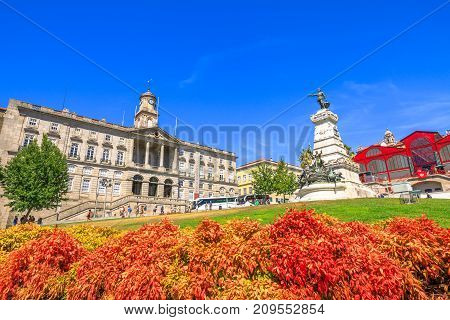 Porto, Portugal - August 11, 2017: coloful Prince Henry Square and Gardens or Jardim do Infante Dom Henrique and Stock Exchange Palace or Palacio da Bolsa, a national monument and Unesco Heritage