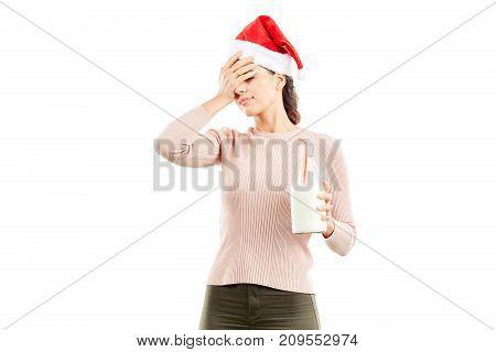 Portrait of woman in Santa hat holding bottle of milk on white background