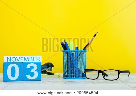 November 3rd. Day 3 of month, wooden color calendar on yellow background with office supplies. Autumn time.