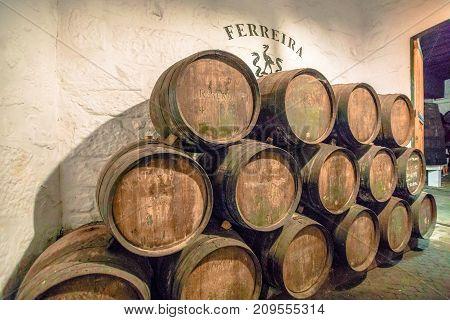 Porto, Portugal - August 13, 2017: Row of wooden porto wine barrels in wine cellar, Ferreira Winery, Vila Nova de Gaia on Douro River, one of the most popular wine tasting tours.