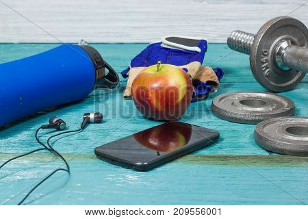 Sport Equipment. Dumbbells, Free Weights, Barbell, Hand Grip, Sport Gloves, Juice, Smart Phone With Earphones To Workout Plan On Wooden Table. Sport Fitness Background