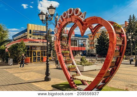 Belgorod, Russia - September 29, 2017: Pedestrian street in the old residential center of the city. Urban environment. Bench of love in the shape of a heart with flower pots near cinema