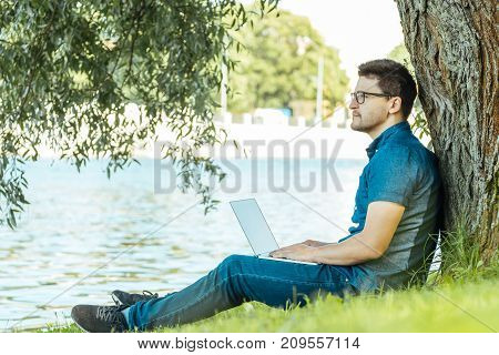 Man With Laptop Sitting Outdoors In Nature