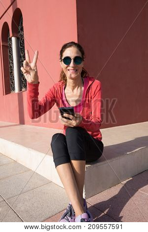 Happy Woman Sitting With Phone And Victory Sign With Fingers