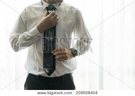 The groom in stylish white shirt adjusts putting his tie. Morning wedding preparation of confident man