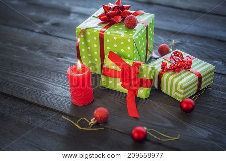 Cheerful image with a bunch of green wrapped gifts tied with red ribbons and bows surrounded by Christmas ornaments and a lit candle on a wooden table.