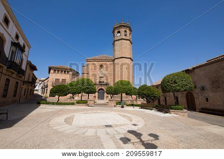 landmark Constitution Square with facade and bell tower of church San Mateo gothic and renaissance from Fifteenth century in old town of Banos de la Encina Jaen Andalusia Spain Europe