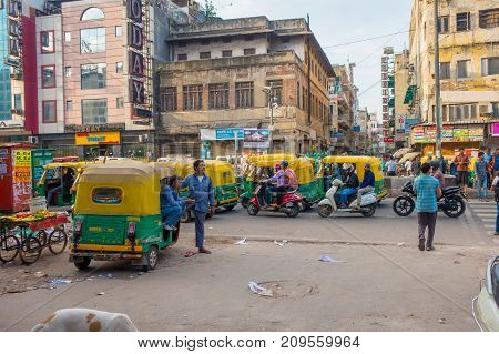 DELHI, INDIA - SEPTEMBER 25 2017: Unidentified people with a green rickshaws and an auto-rickshaws parked in a dirty streets in Paharganj Delhi. Delhi is the 2nd most populous city in India after Mumbai.
