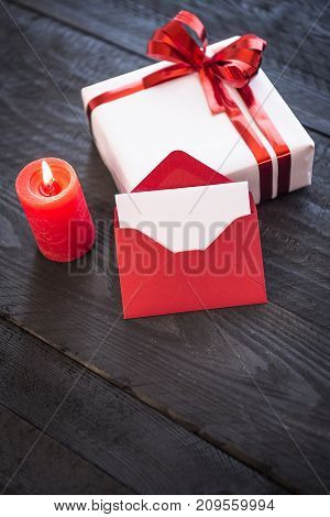 Lit candle red envelope with blank paper leaned against an elegantly wrapped gift box decorated with a red ribbon bow.