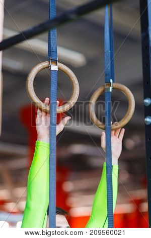Young athlete with gymnastic rings in the gym. Close-up. The concept of sport.
