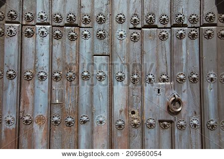 detail of ancient wooden door of church San Mateo from Fifteenth century with metal pieces pattern lock and ring knocker in Banos de la Encina Jaen Andalusia Spain Europe