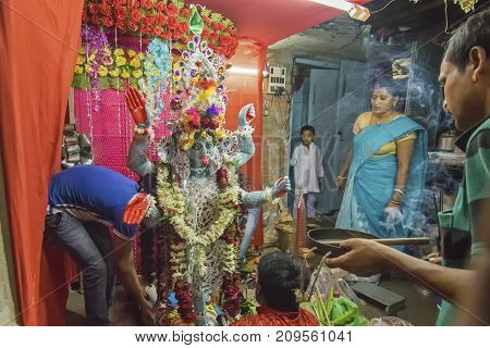 KOLKATA INDIA - JUNE 17 2017 - Hindu devotees worshipping Goddess Kali at night during Kali Puja Hindu festival of Deepavali or Diwali. Celebtated all over India. Shot under mixed light.