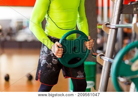 A man in green puts weight on a bar in the gym. Close-up. The concept of sport.