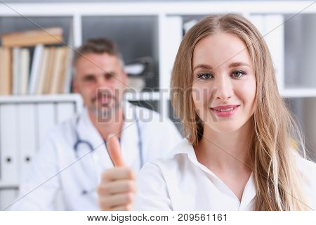 Woman show ok or confirm with thumb up at doctor office portrait. High level work confident satisfied client do like visit best occupation healthy life emergency help teamwork success concept