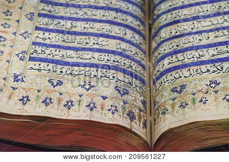 Kuala Lumpur, Malaysia - February 11, 2016: Reading the ancient Holy Quran. The open book at the Islamic Arts Museum in Kuala Lumpur, Malaysia