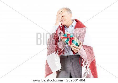 Portrait of senior man wrapped in blanket holding Christmas gift