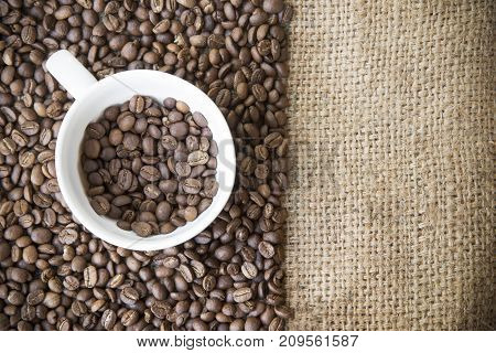 roasted arabica coffee beans in coffee cup with sack cloth background.roasted coffee beans pattern