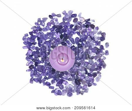 Lavender tea light candle surrounded by amethyst small tumbled chips isolated on white background