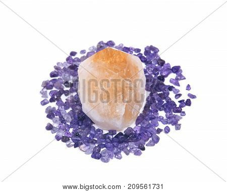 Natural citrine point surrounded by amethyst small tumbled chips isolated on white background