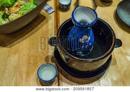 Japanese Hot Sake In Hot Water Bowl On Wooden Table