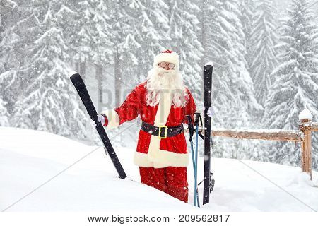 Santa Claus skier on the background of the ski landscape. Vacation in winter in the mountains for Christmas.