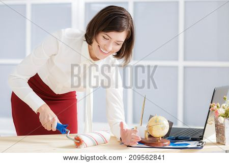 smiling attractive business woman changing activity. woman paints a table with a platen and sheds office items off the table