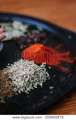 Caraway seeds surrounded by spices on black rustic plate
