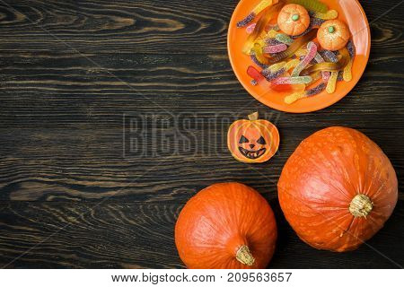 Halloween holiday background with pumpkins and candy. View from above.