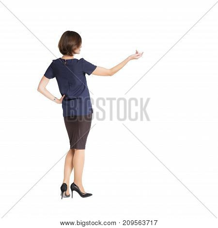 back view of  woman standing and  showing on something or copyspase  isolated on white background
