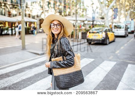 Woman tourist in hat crossing central street during the morning light in Barcelona city