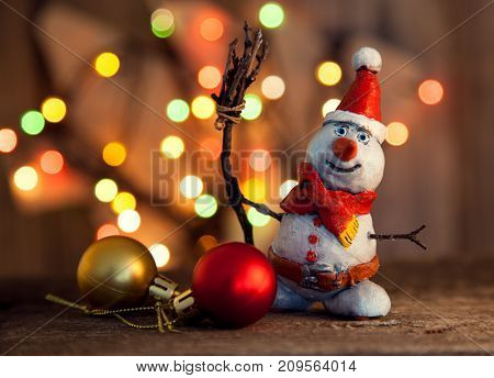 Christmas snowman decoration against the backdrop illumination and fir tree.