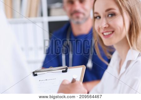 Female doctor arm hold silver pen filling patient complaints list clipped to pad. Physical problem exam disease prevention ward round visitor check prescribe remedy healthy lifestyle concept