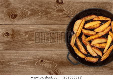 Potato wedges in a cast iron pan on dark wooden background top view
