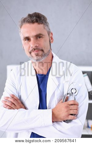 Handsome mature smiling male doctor with arms crossed on chest portrait. Medic store physical and patient disease prevention er consultant 911 profession pulse measure healthy lifestyle concept