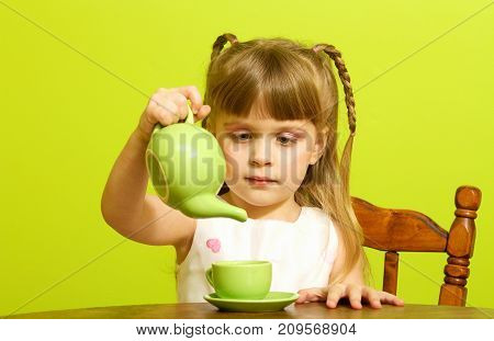 a little girl playing with her tea party set.