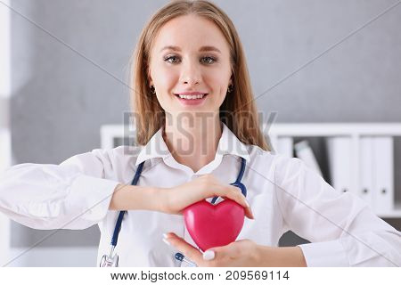 Beautiful smiling blond female doctor hold in arms red toy heart closeup. Cardio therapeutist student education CPR 911 life save physician make cardiac physical pulse rate measure arrhythmia