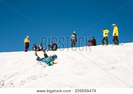 Training to correct slip on a slope or a glacier with the help of an ice ax. A fully equipped backpacker slides on the belly along a snowy slope in the mountains, hindering the glide by an ice ax. in the background there are observing climbers. Training a