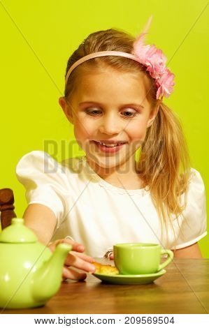 a little girl playing with her tea cup set.