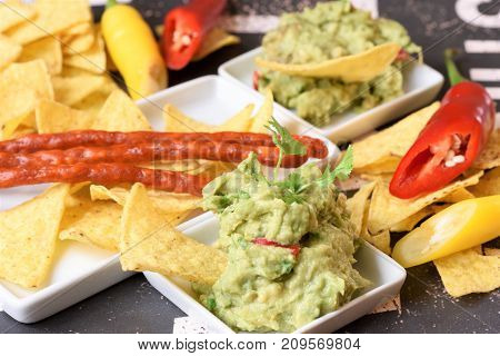 Colorful food, mexican homemade guacamole dip with nachos, spicy sausages and hot chillipepper
