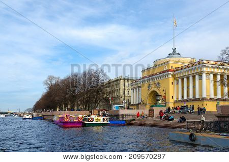 SAINT PETERSBURG RUSSIA - MAY 1 2017: Unknown people are resting on Admiralteiskaya embankment near building of Main Admiralty St. Petersburg Russia