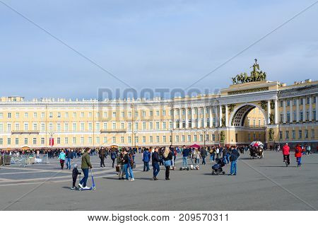 SAINT PETERSBURG RUSSIA - MAY 1 2017: Unknown people walk along Palace Square near Arch of General Staff St. Petersburg Russia