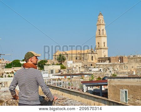 Traveler in front of Lecce rooftop view with the Campanile bell tower of Cattedrale metropolitana di Santa Maria Assunta cathedral in background. Lecce Puglia Italy. poster