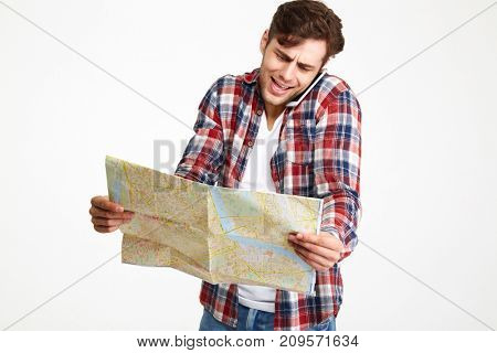 Portrait of a confused young man talking on mobile phone while looking at travel map isolated over white background