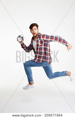 Full length portrait of a troubled young man holding alarm clock while running and looking at camera isolated over white background
