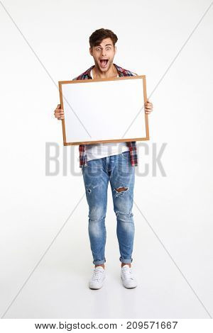 Full length portrait of an amused cheerful guy holding blank board and looking at camera isolated over white background