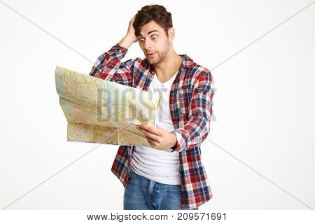 Portrait of a mixed-up young man looking at travel map isolated over white background