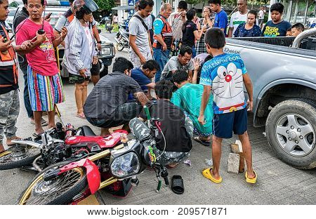 BANGKOK THAILAND - OCTOBER 14: Rescue Workers get to work to assist a man in a motorcycle traffic accident while surrounded by onlookers including children in Bangkok on October 14 2017.
