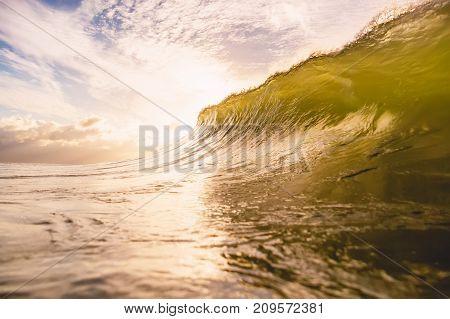 Wave in ocean at sunset or sunrise. Wave crashing at sunrise